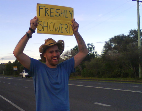 "Hitchhiker with a sign saying ""Freshly Shower'd"""